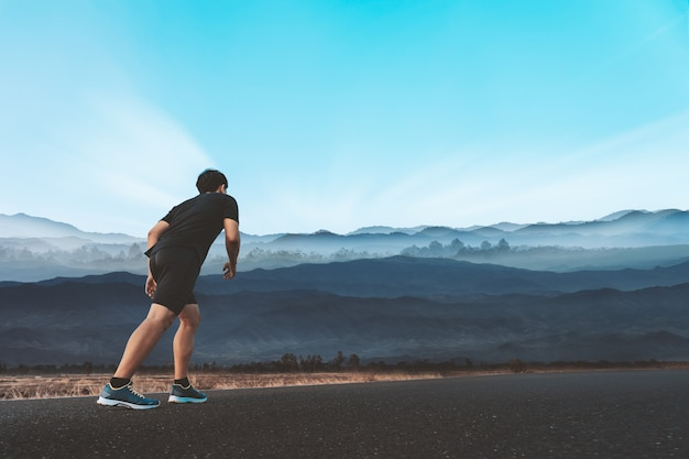 Jeune homme aime courir à l'extérieur avec une belle soirée d'été à la campagne. Photo Premium