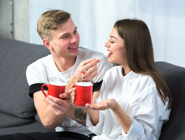 Jeune homme, alimentation, femme, à, guimauve, sur, divan Photo gratuit