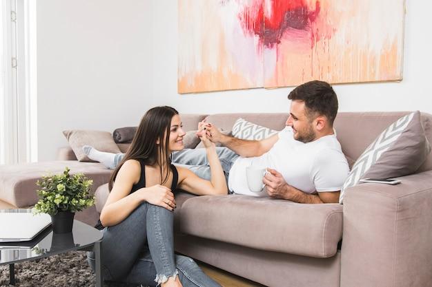 Jeune homme allongé sur un canapé tenant la main de sa petite amie assis sur le sol Photo gratuit