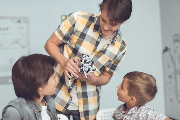 Le jeune homme a amené un robot gris à deux garçons Photo Premium