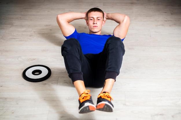 Jeune homme à l'angle élevé à l'entraînement de gym Photo gratuit