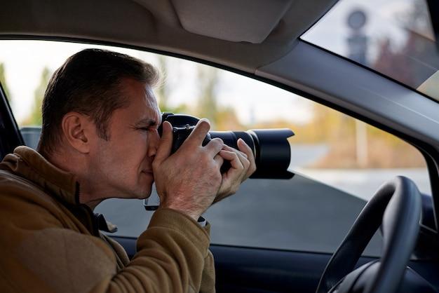 Jeune Homme Avec Un Appareil Photo Reflex Numérique Dans Une Voiture Photo Premium