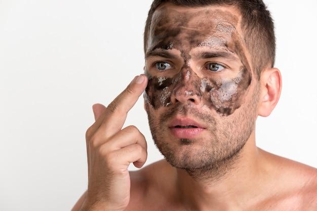 Jeune homme appliquant un masque noir sur son visage sur fond blanc Photo gratuit