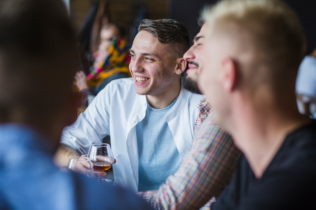 Jeune homme appréciant des boissons avec ses amis Photo gratuit