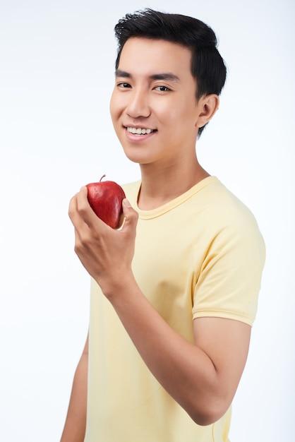Jeune homme appréciant une pomme savoureuse Photo gratuit