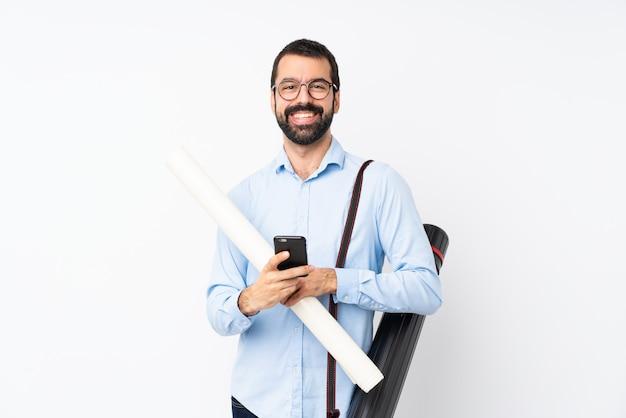 Jeune homme architecte avec barbe sur blanc isolé en envoyant un message avec le mobile Photo Premium
