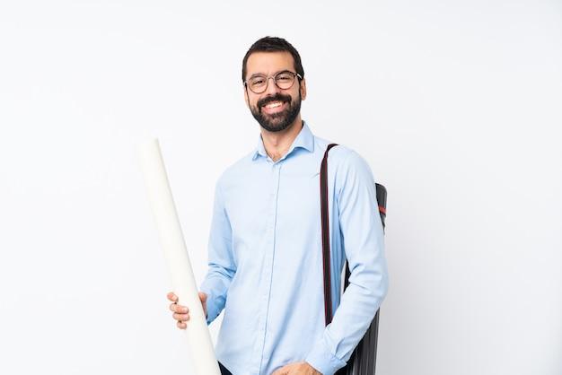 Jeune homme architecte avec barbe sur blanc isolé rire Photo Premium