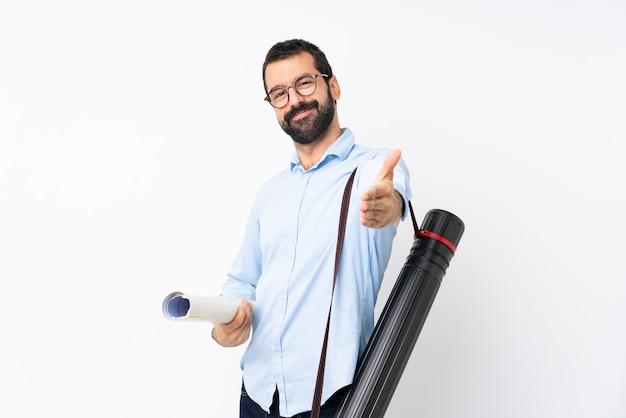 Jeune homme architecte avec barbe sur blanc isolé se serrant la main pour fermer une bonne affaire Photo Premium