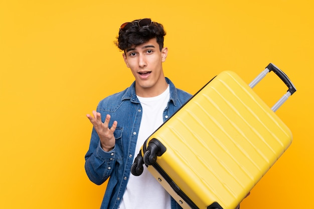 Jeune Homme Argentin Sur Fond Jaune Isolé En Vacances Avec Valise De Voyage Photo Premium