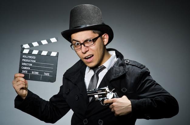 Jeune homme avec arme et clins contre gris Photo Premium