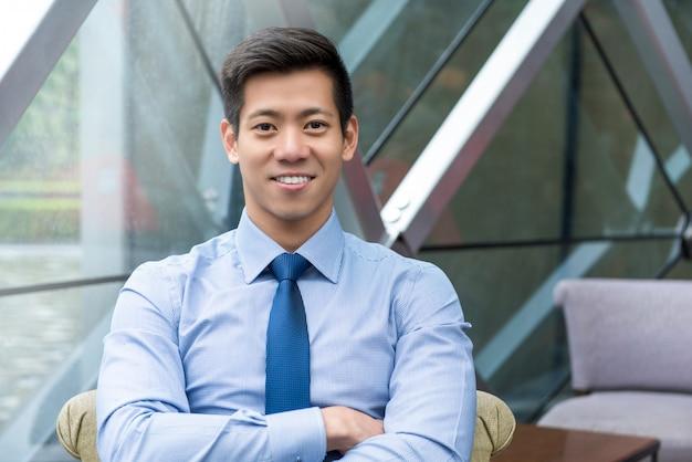 Jeune homme asiatique beau souriant assis dans le salon du bureau Photo Premium