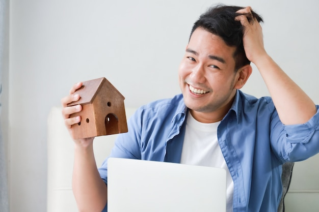 Jeune homme asiatique en chemise bleue avec ordinateur portable et petit modèle de maison montrant pour prêt bancaire pour concept de maison dans le salon Photo Premium