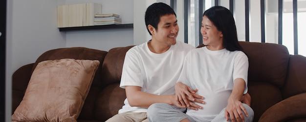Jeune homme asiatique de couple enceinte touche le ventre de sa femme en discutant avec son enfant. maman et papa se sentent heureux, souriant, paisible, tout en prenant soin de bébé, grossesse allongée sur le canapé du salon à la maison Photo gratuit