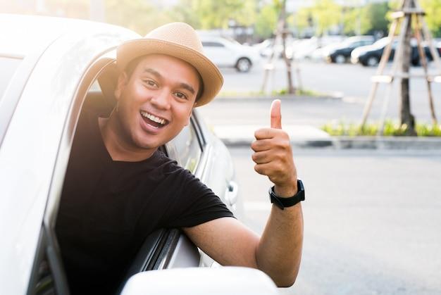 Jeune Homme Asiatique Montrant Les Pouces Vers Le Haut En Conduisant La Voiture Photo Premium