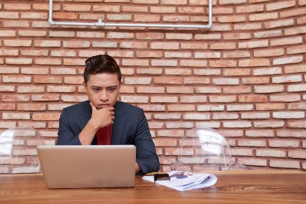 Jeune homme asiatique regardant un écran d'ordinateur portable et se frottant le menton Photo gratuit