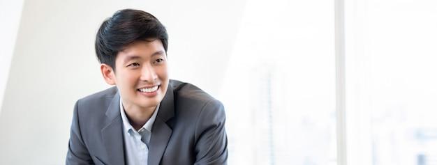 Jeune homme asiatique souriant sur fond de bannière de bureau blanc Photo Premium
