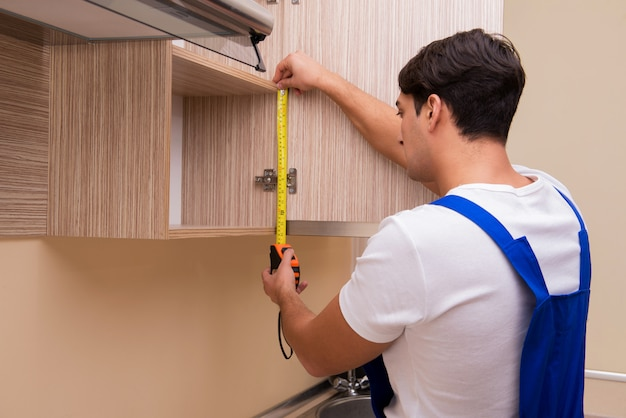 Jeune homme assemblant des meubles de cuisine Photo Premium