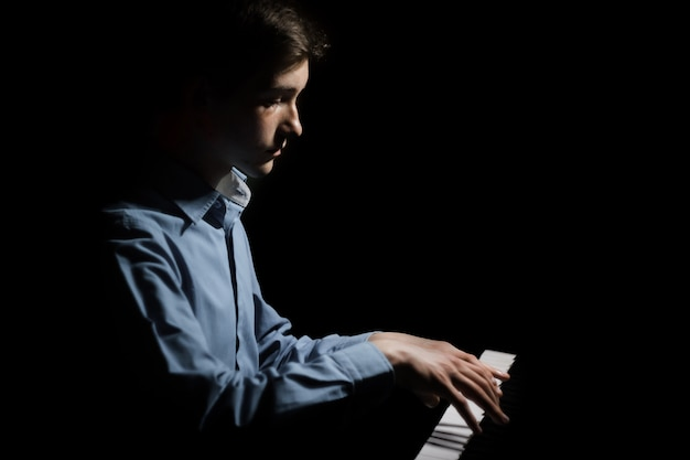 Jeune homme assis au piano. Photo Premium