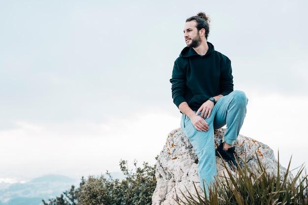 Jeune homme assis au sommet d'un rocher en regardant la vue Photo gratuit