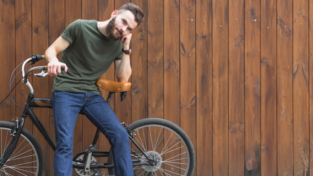 Jeune homme assis sur une bicyclette sur un fond en bois Photo gratuit