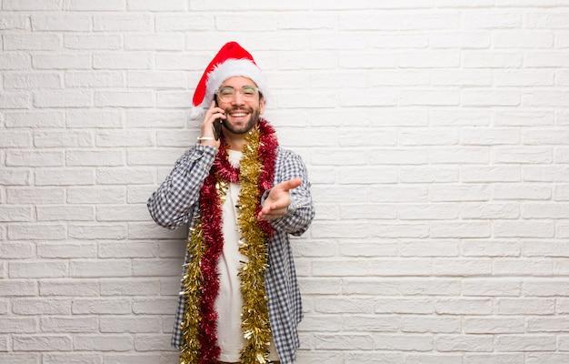 Jeune Homme Assis Avec Des Cadeaux Pour Célébrer Noël Tendre La Main Pour Saluer Quelqu'un Photo Premium