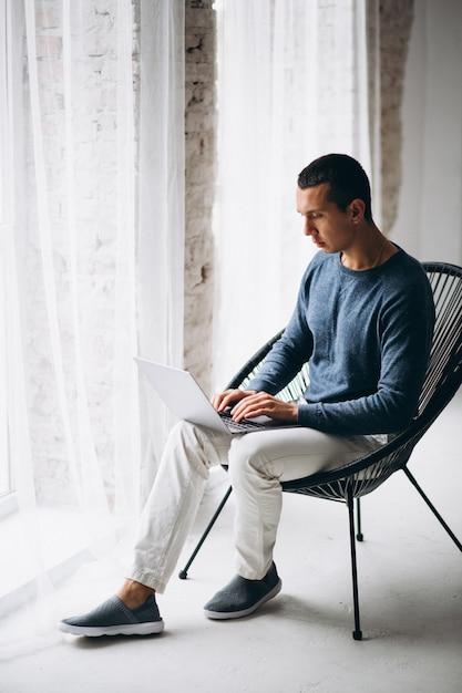 Jeune Homme Assis Sur Une Chaise Et Utilisant Un Ordinateur Portable Photo gratuit