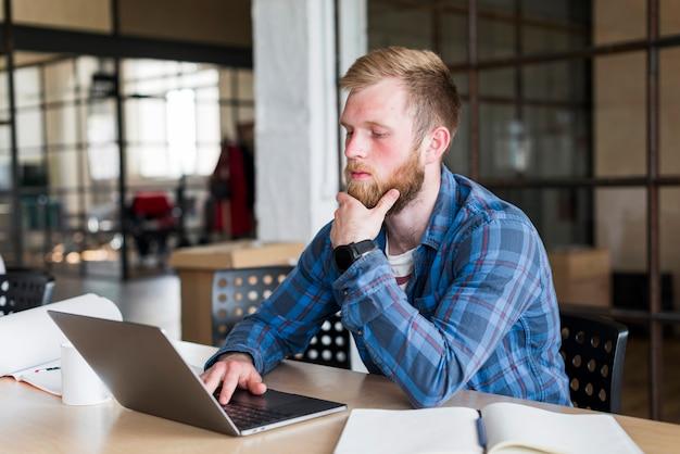 Jeune homme assis dans le bureau à l'aide d'un ordinateur portable Photo gratuit