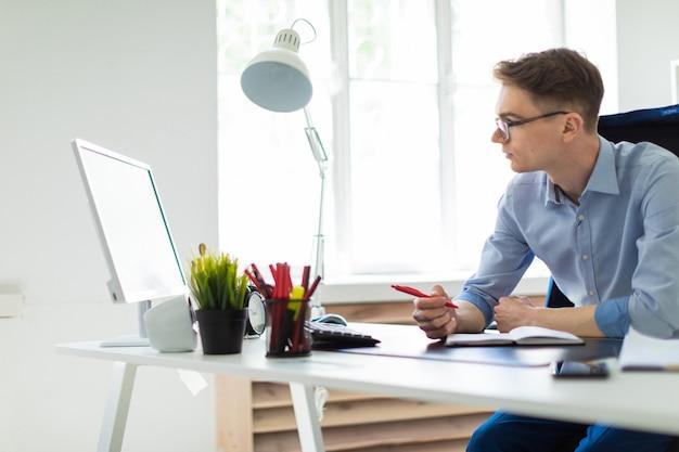 Un jeune homme assis dans le bureau au bureau de l'ordinateur tient un stylo à la main et regarde l'écran. Photo Premium