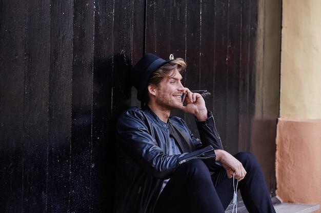 Jeune homme assis dans la rue Photo Premium
