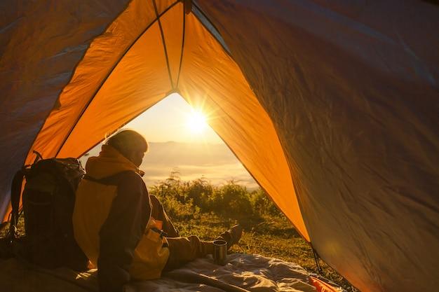 Un jeune homme assis dans la tente, regardant le paysage de montagne en hiver Photo gratuit