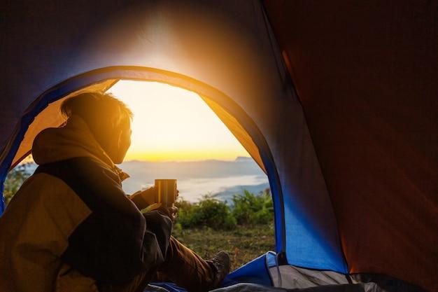 Un jeune homme assis dans la tente avec une tasse de café Photo gratuit