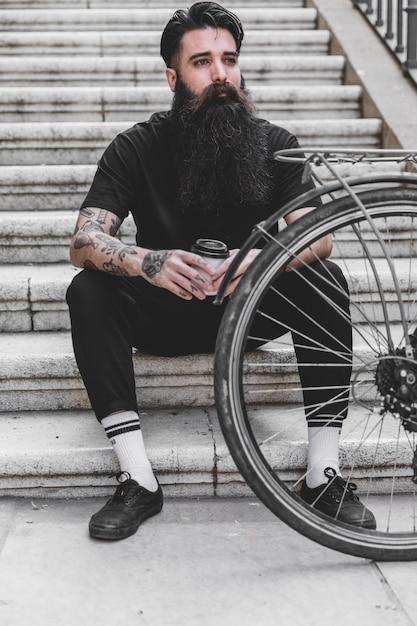 Jeune homme assis sur un escalier tenant une tasse de café jetable Photo gratuit