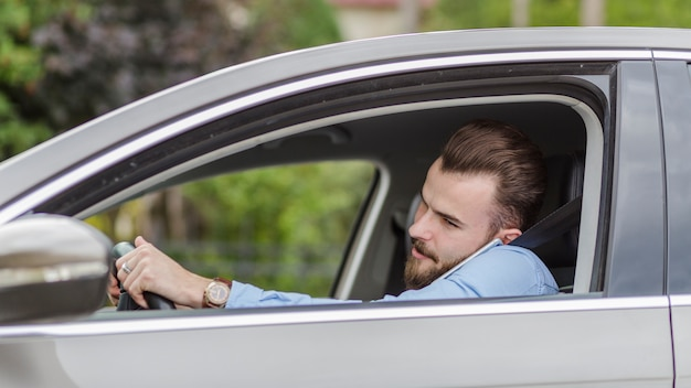 Jeune homme assis à l'intérieur d'une voiture parlant au téléphone Photo gratuit