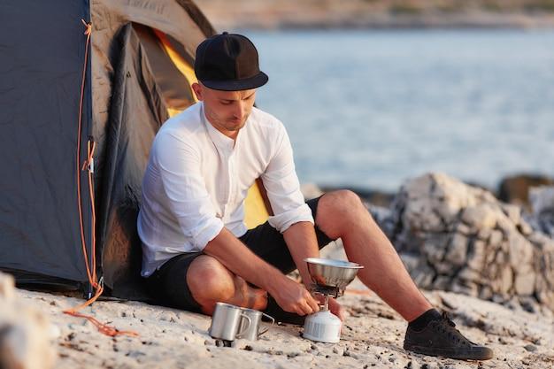 Jeune Homme Assis Sur Un Rivage Rocheux Près De La Tente, Pose De Dalle De Gaz. Photo Premium