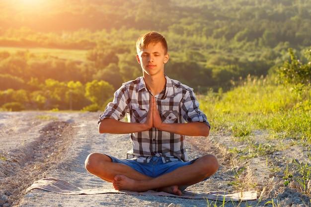Jeune homme assis sur la route en position de lotus par une journée ensoleillée Photo Premium