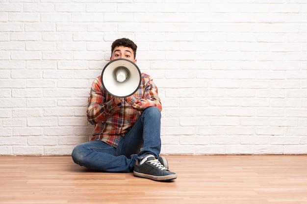 Jeune homme assis sur le sol en criant à travers un mégaphone Photo Premium