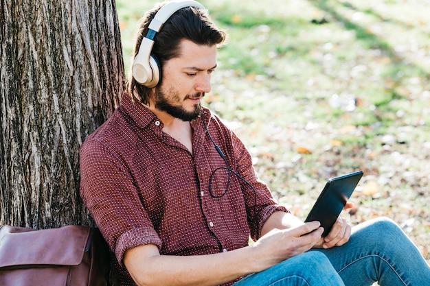 Jeune homme assis sous l'arbre écouter de la musique sur un casque via un téléphone mobile Photo gratuit