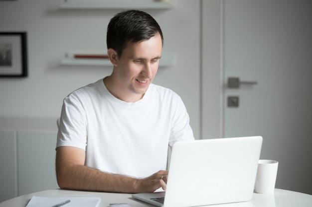 Jeune homme assis à la table blanche travaillant avec un ordinateur portable Photo gratuit