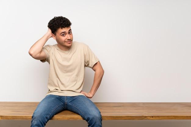 Jeune homme assis sur une table en pensant à une idée Photo Premium