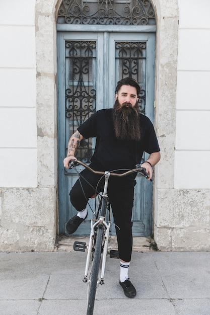 Jeune homme assis sur un vélo devant la porte bleue fermée Photo gratuit