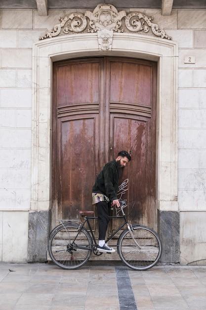 Jeune homme assis sur le vélo devant la porte en bois vintage Photo gratuit