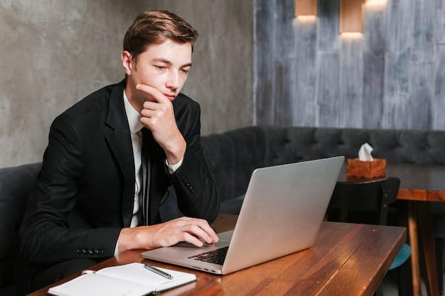 Jeune homme au bureau travaillant sur l'ordinateur portable Photo gratuit