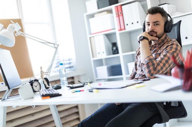 Un jeune homme au casque est assis à une table dans le bureau et regarde l'écran. Photo Premium