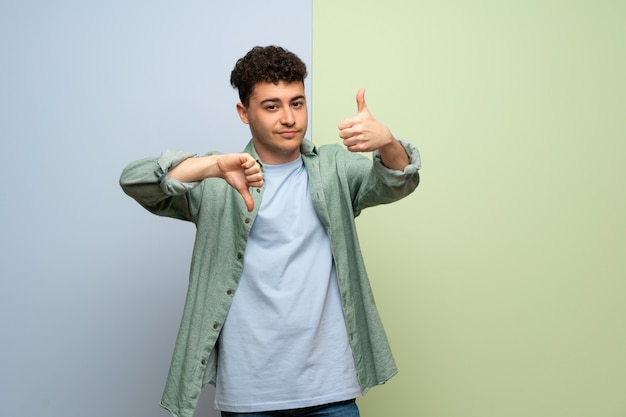 Jeune homme au-dessus de bleu et vert faisant signe bon-mauvais. indécis entre oui ou non Photo Premium