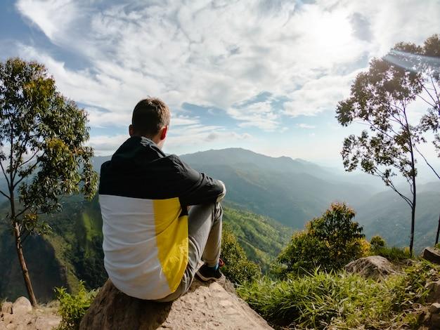 Un Jeune Homme Au Sommet Est Assis Sur Une Pierre Près De Ella, Au Sri Lanka Photo Premium