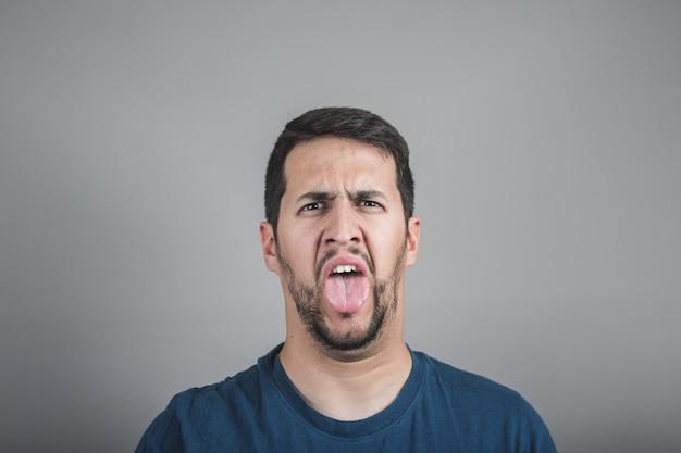Jeune homme au visage dégoûtant qui tire la langue Photo Premium