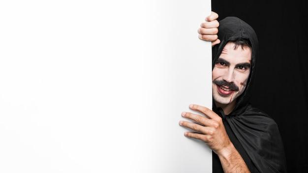Jeune homme au visage pâle en manteau noir qui pose en studio Photo gratuit