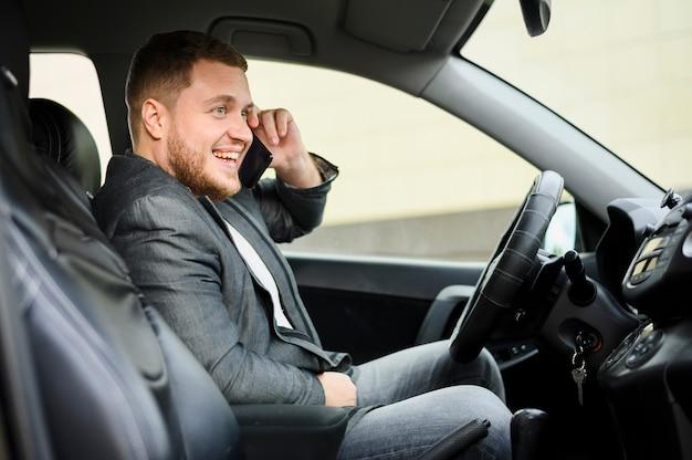 Jeune homme au volant avec son téléphone à l'oreille Photo gratuit