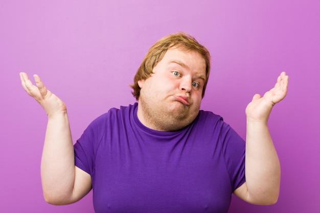 Jeune homme authentique de graisse rousse doutant et haussant les épaules en un geste interrogatif. Photo Premium