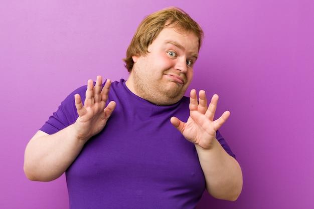 Jeune homme authentique, gros homme à la rouquine, rejetant une personne montrant un geste de dégoût. Photo Premium